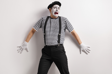 Terrified mime against a wall