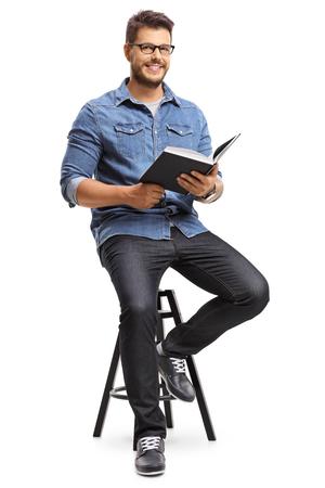 Hombre con un libro sentado en una silla y mirando a la cámara aislada sobre fondo blanco Foto de archivo - 81550236