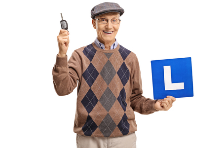 Elderly man holding a car key and an L-sign isolated on white background