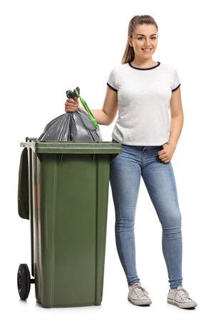 白い背景に分離されたゴミを捨てて若い女の子の完全な長さの肖像画