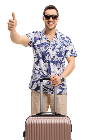 Tourist with a suitcase making a thumb up gesture isolated on white background