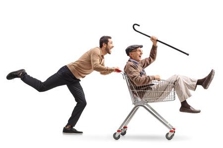 若い男に分離の白い背景の中上級とショッピングカートを押す