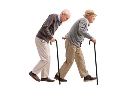 back ache: Full length profile shot of two elderly men with canes walking isolated on white background Stock Photo