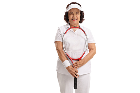 70s tennis: Elderly tennis player with a racket looking at the camera isolated on white background