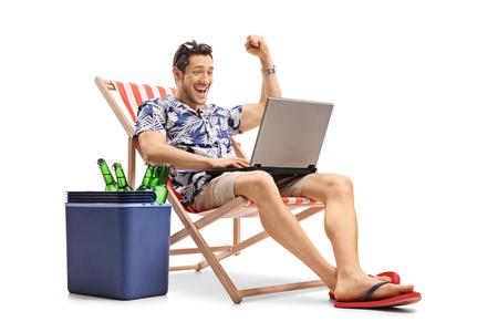 Blije toerist met een laptop zitting in een ligstoel naast een koelvakje met flessen bier dat op witte achtergrond wordt geïsoleerd
