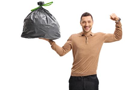 Giovane che tiene un sacchetto di immondizia e che flette il suo bicipite isolato su fondo bianco Archivio Fotografico