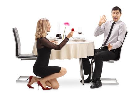Jonge vrouw die voor haar geschokte vriendin voorstelt aan een restaurant tafel geïsoleerd op een witte achtergrond