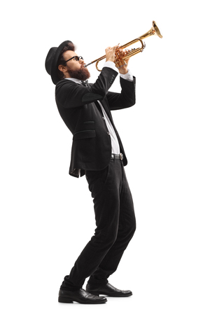Full length profile shot of a musician playing a trumpet isolated on white background
