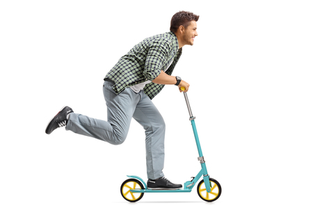 Profile shot of a young man riding a scooter isolated on white background Foto de archivo