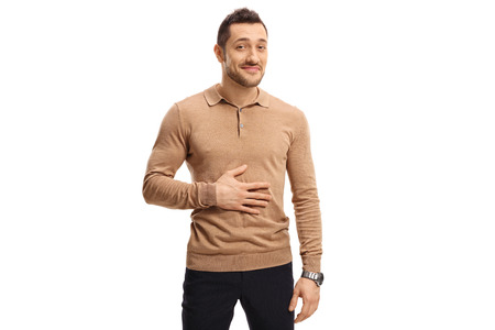 Satisfied man holding his hand on his stomach after having a meal or a drink isolated on white background