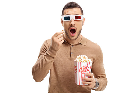 Scared guy with a pair of 3D glasses and popcorn isolated on white background