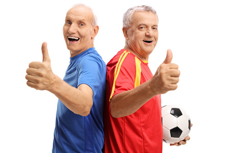 Cheerful elderly soccer players holding their thumbs up isolated on white background Stock Photo