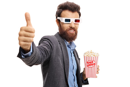 Bearded guy with 3D glasses and popcorn making a thumb up gesture isolated on white background