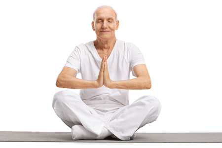 equilibrium: Senior meditating on an exercise mat isolated on white background