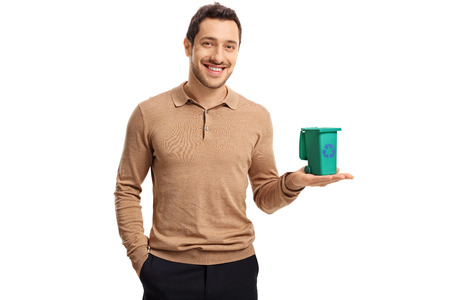 Young guy holding a small recycling bin and smiling isolated on white background Stock Photo