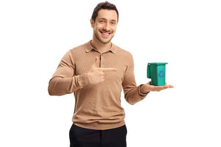 Young guy holding a small recycle bin and pointing isolated on white background