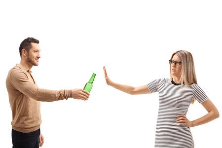 白い背景で隔離のビールのボトルを拒否した若い女性