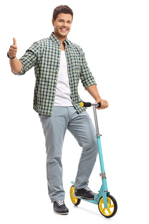 Full length portrait of a young guy with a scooter making a thumb up gesture isolated on white background photo