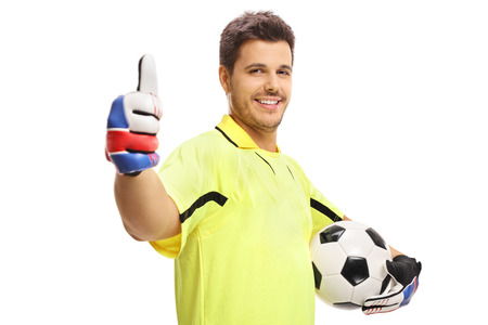 Goalkeeper holding a football and making a thumb up sign isolated on white background