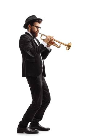 Full length profile shot of a trumpet player isolated on white background