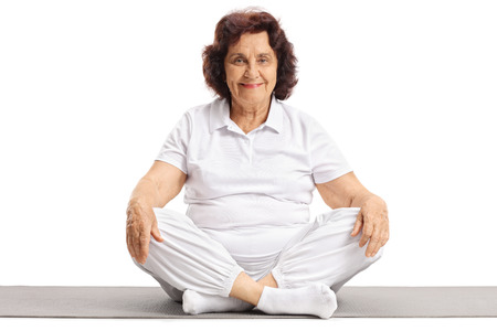 Mature woman sitting on an exercise mat isolated on white background