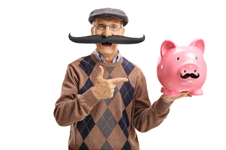 70s: Elderly man with fake moustache pointing at a piggybank with fake moustache isolated on white background