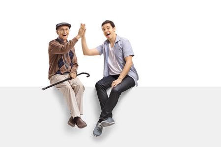 Senior y un hombre joven de alta fiving el uno al otro en un panel y mirando a la cámara aislada sobre fondo blanco