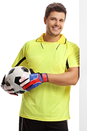 Goalkeeper with a football leaning against a wall isolated on white background photo