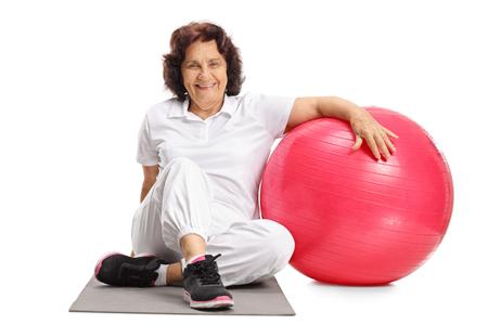 Bejaardezitting op een oefeningsmat naast een pilatesbal die op witte achtergrond wordt geïsoleerd