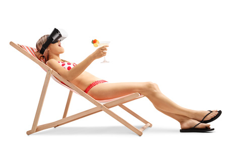 chairs: Young woman with a cocktail in a deck chair using a VR headset isolated on white background Stock Photo