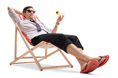 Businessman with a cocktail relaxing in a deck chair isolated on white background