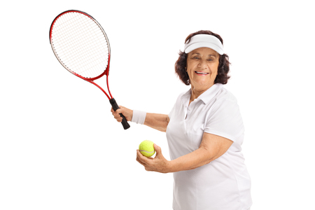 70s tennis: Elderly tennis player preparing to serve isolated on white background