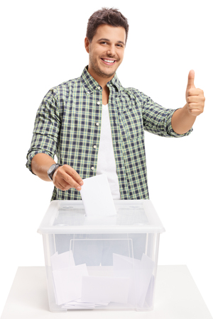 若い男の投票と、白い背景で隔離のサインを親指を作る 写真素材