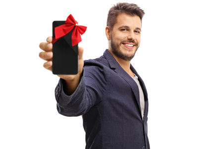 Elegant guy showing a phone wrapped with red ribbon as a present and smiling isolated on white background photo