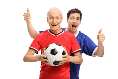 Senior in a jersey holding a football with a young man behind him holding his thumbs up isolated on white background photo