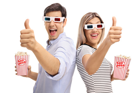 Young man and a young woman with 3D glasses and popcorn holding their thumbs up isolated on white background photo