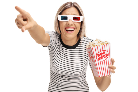Young woman with 3D glasses and popcorn pointing and laughing isolated on white background photo