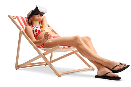 Young woman with a cocktail lying in a deck chair and using a VR headset isolated on white background photo