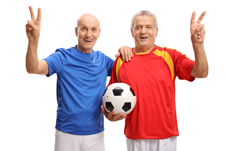 Elderly soccer players holding a football and making victory signs isolated on white background photo