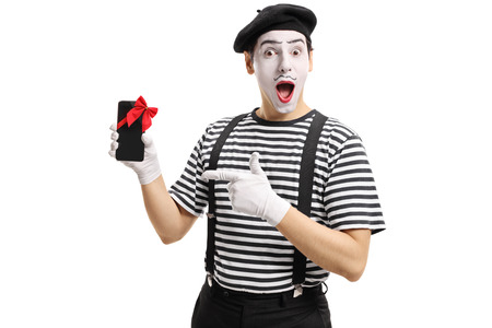 Mime artist showing a phone wrapped with red ribbon as a present and pointing isolated on white background Stock Photo