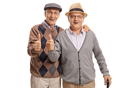 Seniors looking at the camera and holding their thumbs up isolated on white background Stock Photo