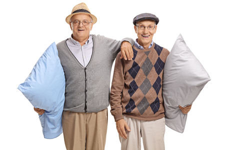Two elderly men with pillows looking at the camera and smiling isolated on white background photo