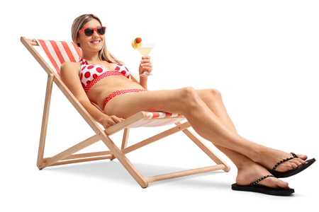 Young woman with a cocktail relaxing in a deck chair isolated on white background photo