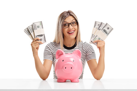 Cheerful woman behind a table with bundles of money and a piggybank isolated on white background photo