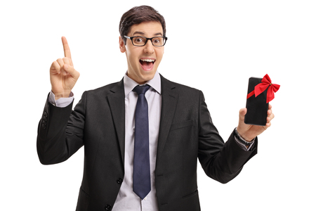 Cheerful businessman showing a phone wrapped with red ribbon as a gift and pointing up isolated on white background photo
