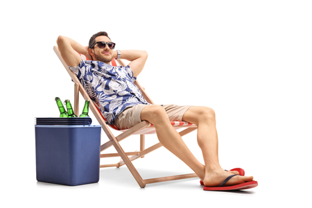 Tourist relaxing in a deck chair next to a cooling box filled with bottles of beer isolated on white background