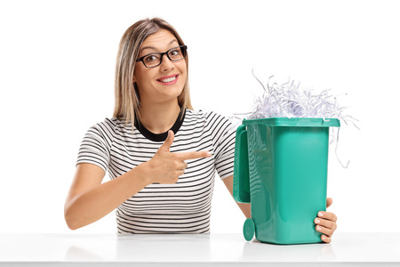 Young woman sitting at a table and pointing at a garbage bin full of shredded paper isolated on white background