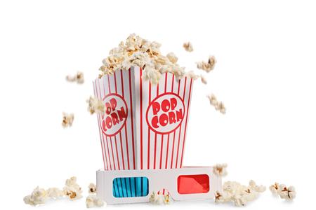 Scatola traboccante di popcorn e un paio di occhiali 3D isolati su sfondo bianco
