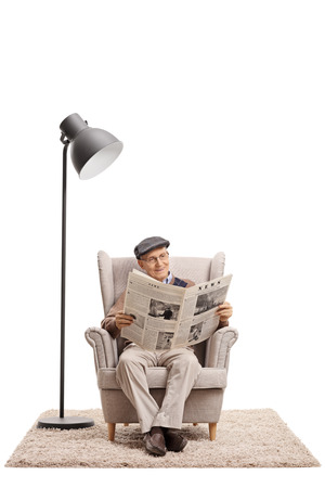 Elderly man reading a newspaper in an armchair next to a lamp isolated on white background Foto de archivo