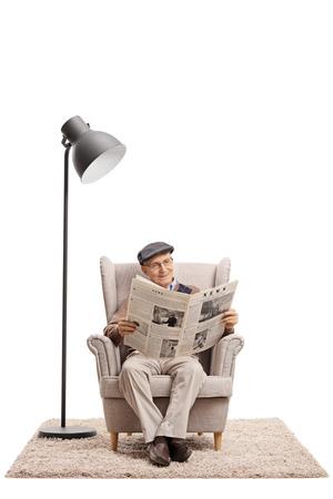 Hombre mayor leyendo un periódico en un sillón junto a una lámpara aislada sobre fondo blanco Foto de archivo - 84246998
